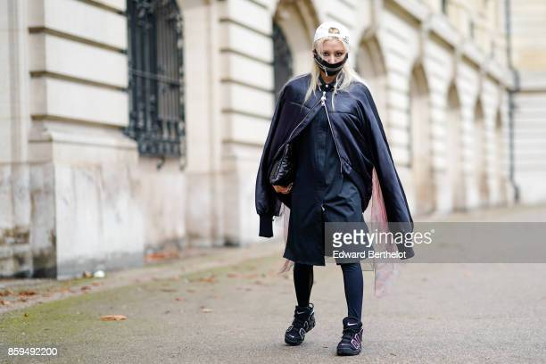 A guest wears a petrol blue jacket a petrol blue dress a white cap black tights and petrol blue trainers outside Manish Arora during Paris Fashion...