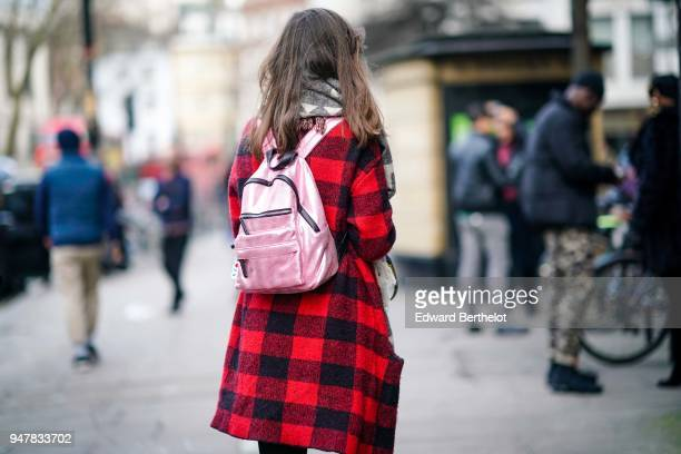 A guest wears a pink bag a red gingham coat during London Fashion Week Men's January 2018 at on January 6 2018 in London England