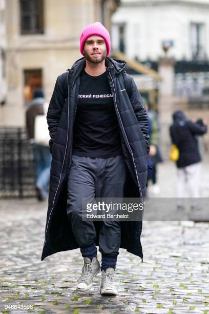 A guest wears a pink beanie hat a gray puffer coat a black top gray pants white shoes outside Thom Browne during Paris Fashion Week Menswear Fall...