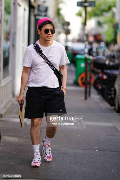 A guest wears a pink beanie hat sunglasses a white tshirt black short sneakers shoes white socks a Givenchy strap outside Yohji Yamamoto during Paris...