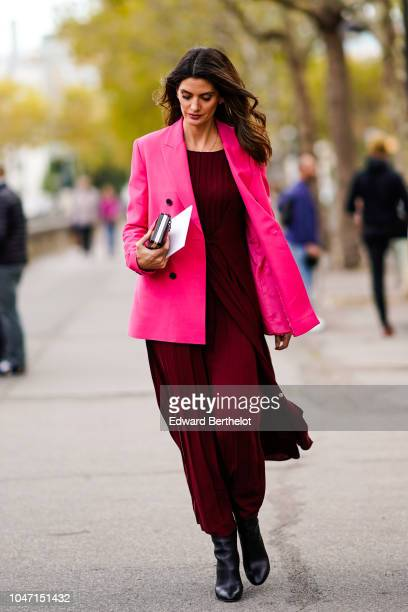 A guest wears a pink blazer jacket a red burgundy dress black leather boots outside Valentino during Paris Fashion Week Womenswear Spring/Summer 2019...