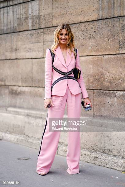 A guest wears a pink blazer jacket flared pants outside Elie Saab during Paris Fashion Week Haute Couture Fall Winter 2018/2019 on July 4 2018 in...