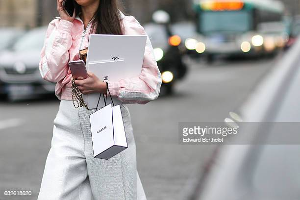 A guest wears a pink bomber jacket a Chanel bag white pants pink shoes and holds a pink iphone outside the Chanel show at the Grand Palais during...