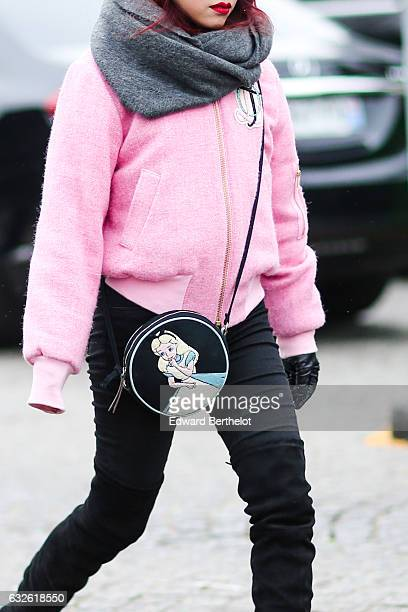 A guest wears a pink bomber jacket a gray scarf and a bag with a print representing Cinderella outside the Chanel show at the Grand Palais during...
