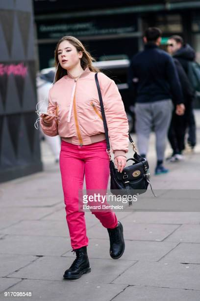A guest wears a pink bomber jacket pink pants during London Fashion Week Men's January 2018 at on January 6 2018 in London England