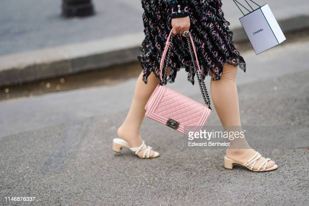 Guest wears a pink Chanel Boy bag, outside the Chanel Cruise Collection 2020 At Grand Palais on May 03, 2019 in Paris, France.