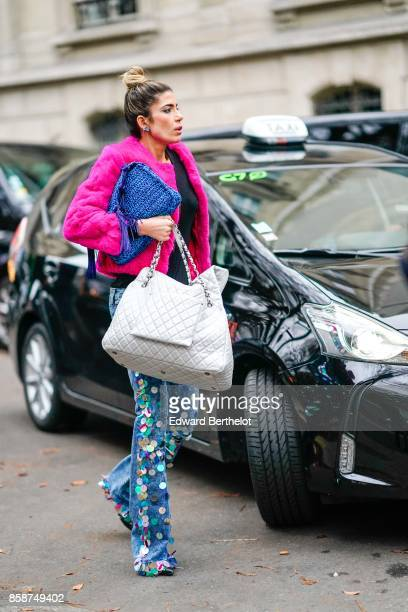 A guest wears a pink coat a large white bag flower print pants outside John Galliano during Paris Fashion Week Womenswear Spring/Summer 2018 on...