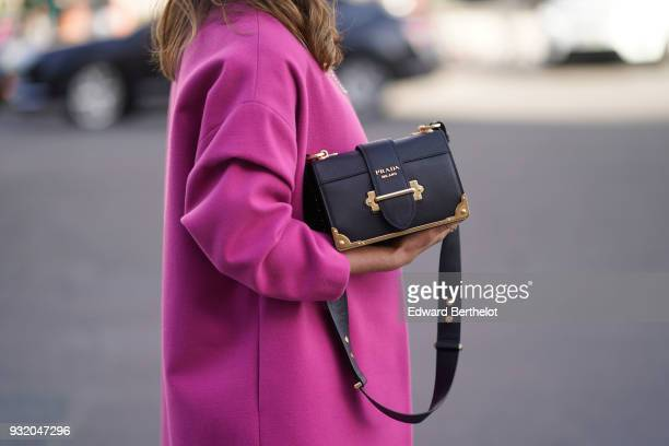 A guest wears a pink coat and a Prada bag during Paris Fashion Week Womenswear Fall/Winter 2018/2019 on March 3 2018 in Paris France
