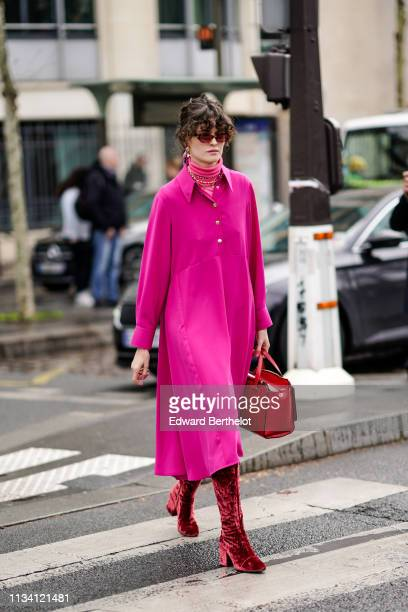 Guest wears a pink coat, turtleneck top, a red bag, red boots, outside Miu Miu, during Paris Fashion Week Womenswear Fall/Winter 2019/2020, on March...