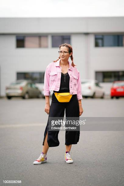 A guest wears a pink denim jacket a yellow belt bag during Feeric Fashion Week 2018 on July 20 2018 in Sibiu Romania