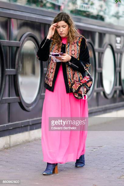 A guest wears a pink dress a jacket with embroidered flowers a bag outside Roland Mouret during London Fashion Week September 2017 on September 17...