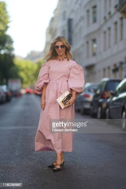 A guest wears a pink dress with large sleeves sunglasses shoes outside Valentino during Paris Fashion Week Haute Couture Fall/Winter 2019/2020 on...