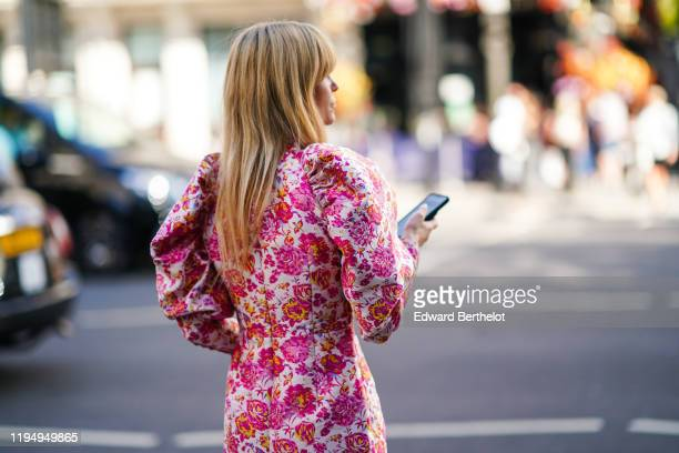A guest wears a pink floral print dress with shoulder pads during London Fashion Week September 2019 on September 15 2019 in London England
