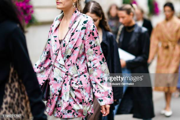 Guest wears a pink floral print kimono dress, during London Fashion Week September 2019 on September 16, 2019 in London, England.