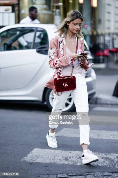A guest wears a pink floral print shirt white pants a red Gucci bag white ripped denim jeans pants white sneakers outside the Fendi during Paris...