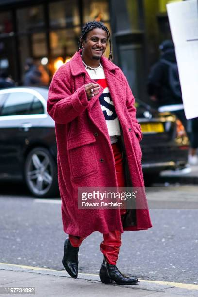 A guest wears a pink fluffy long coat red pants black leather pointy shoes a pearl necklace a wool pullover during London Fashion Week Men's January...