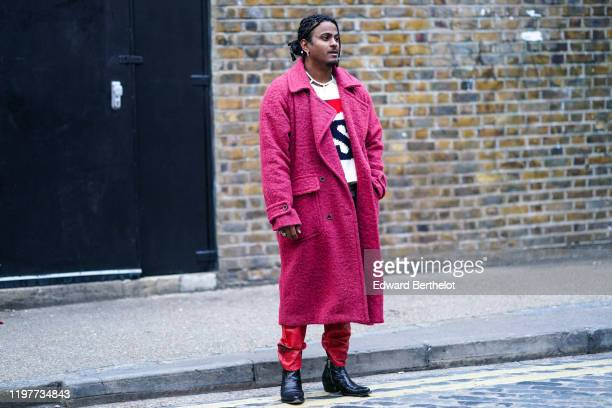 A guest wears a pink fluffy long coat red pants black leather pointy shoes during London Fashion Week Men's January 2020 on January 05 2020 in London...