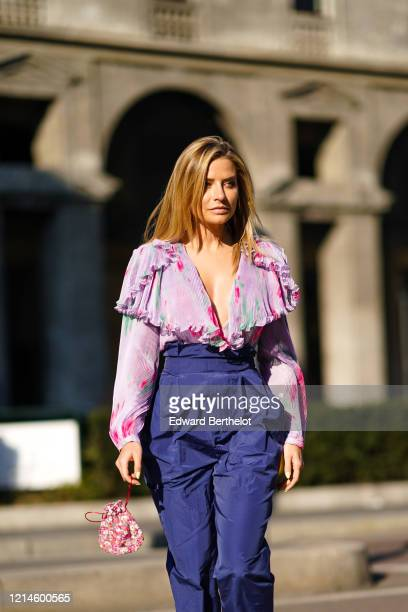 Guest wears a pink frilly floral print top with a plunging neckline, lustrous navy blue pleated high-rise pants, outside Philosophy, during Milan...