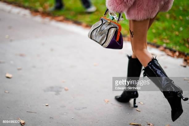A guest wears a pink fur coat a taupe and black snake print leather bag highheeled black patent leather boots outside the Rochas show during Paris...