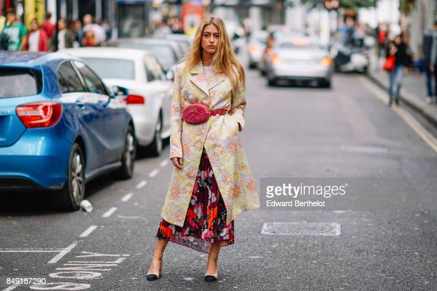 A guest wears a pink Gucci bag a jacket with embroidered flowers a flower print dress and Chanel slingback shoes outside Topshop during London...