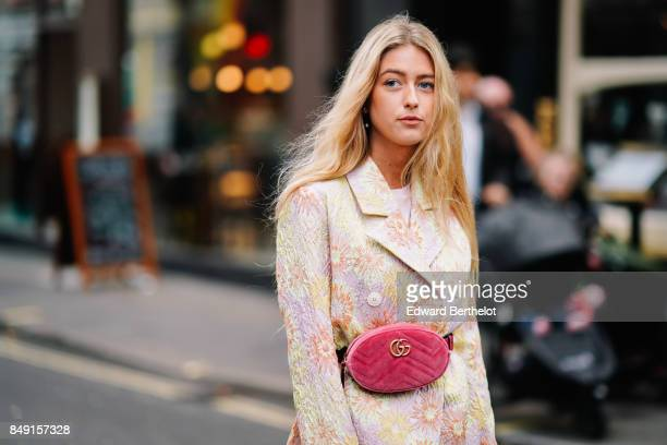 A guest wears a pink Gucci bag a jacket with embroidered flowers a flower print dress outside Topshop during London Fashion Week September 2017 on...