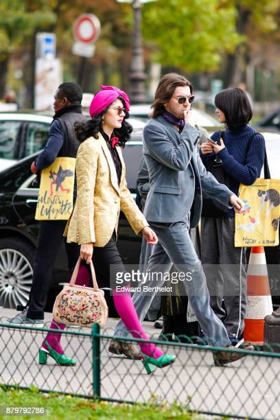 A guest wears a pink hat sunglasses a yellow blazer jacket black skirt pink tights green shoes a color bag outside Margiela during Paris Fashion Week...