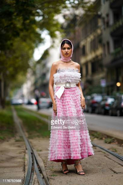 Guest wears a pink head scarf with white polka dots, a bejeweled white frilly bustier, a white belt with a bejeweled buckle, a white transparent...