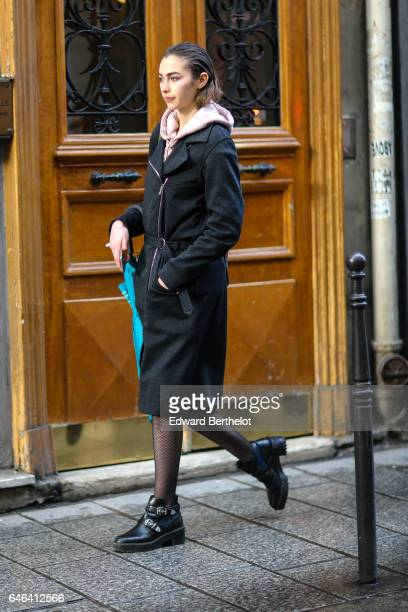A guest wears a pink hoodie a black coat black fishnet tights and black shoes outside the AALTO show during Paris Fashion Week Womenswear Fall/Winter...