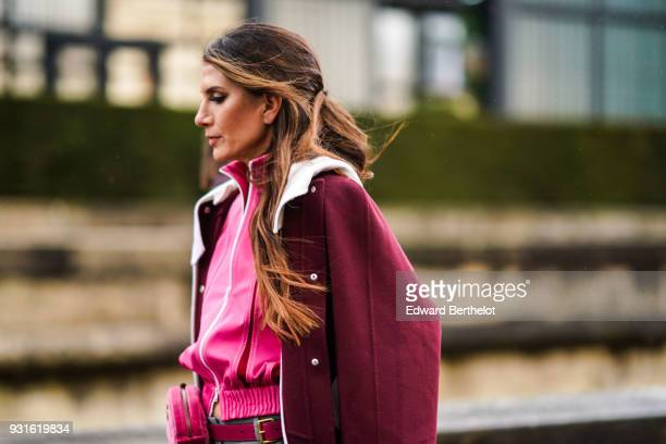 A guest wears a pink jacket a carmine red coat with a white collar a pink belt bag outside Valentino during Paris Fashion Week Womenswear Fall/Winter...