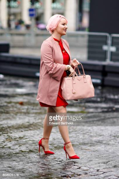 A guest wears a pink jacket a pink bag a red dress red shoes has pink hair and attends Le Defile L'Oreal Paris as part of Paris Fashion Week...