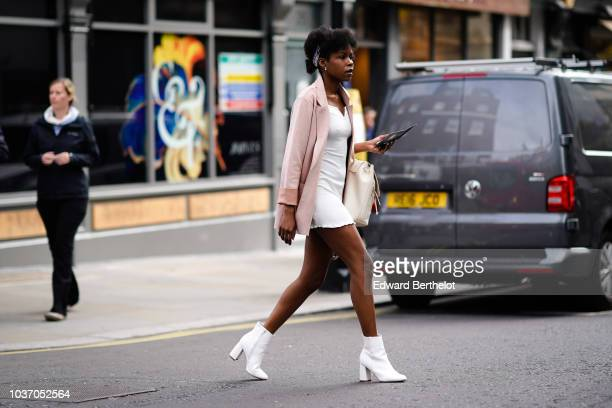 Guest wears a pink jacket, a white dress, white boots, during London Fashion Week September 2018 on September 14, 2018 in London, England.
