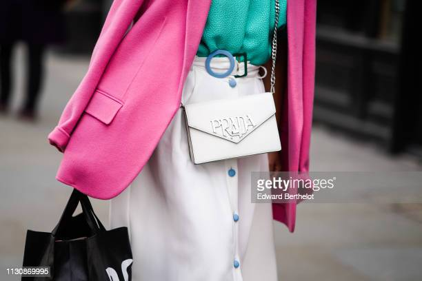 A guest wears a pink jacket a white skirt with a blue round buckle and blue buttons a white Prada bag during London Fashion Week February 2019 on...