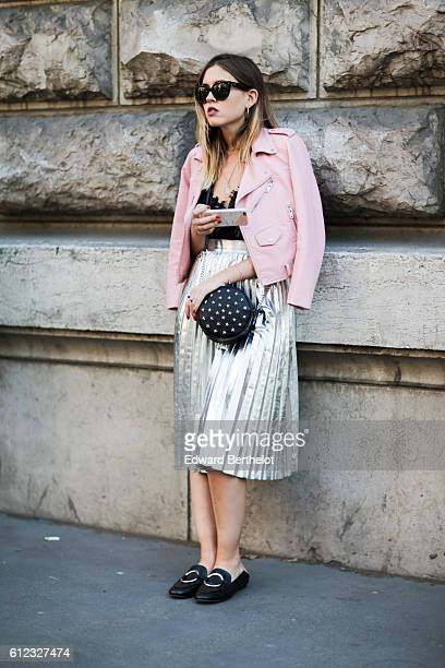 A guest wears a pink jacket and a silver dress outside of the Hermes show during Paris Fashion Week Spring Summer 2017 on October 3 2016 in Paris...