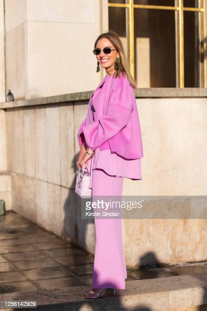 Guest wears a pink jacket and trousers, Dior bag and Polaroid sunglasses on February 26, 2020 in Paris, France.