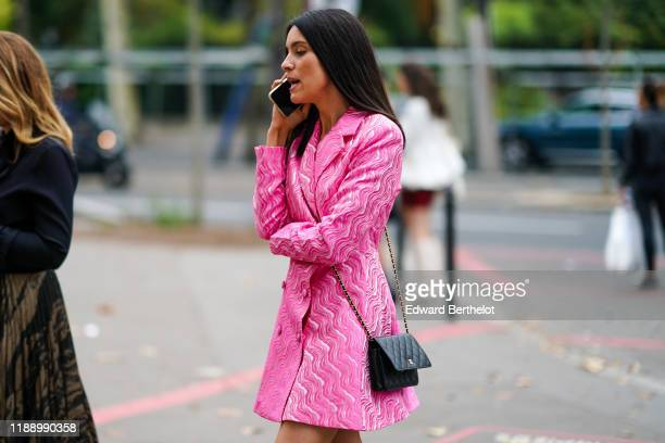 Guest wears a pink jacket dress with printed waves patterns, a black Chanel bag, outside Nina Ricci, during Paris Fashion Week - Womenswear Spring...