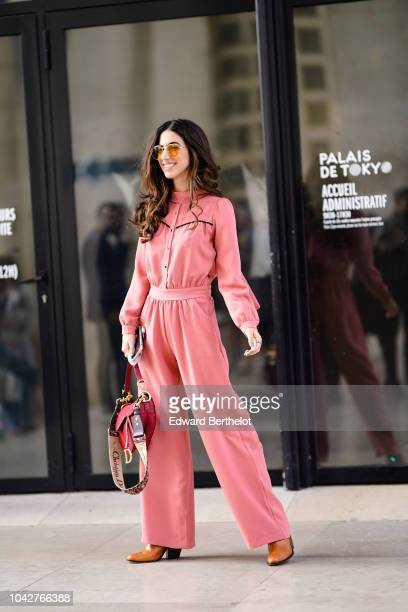 Guest wears a pink jumpsuit and a Dior red Saddle bag, outside Issey Miyake, during Paris Fashion Week Womenswear Spring/Summer 2019, on September...