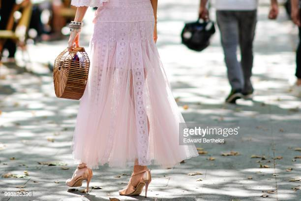 A guest wears a pink lace dress a basket bag during Paris Fashion Week Haute Couture Fall Winter 2018/2019 on July 4 2018 in Paris France