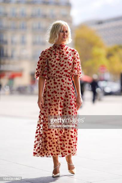 A guest wears a pink lace dress with red printed hearts outside Giambattista Valli during Paris Fashion Week Womenswear Spring/Summer 2019 on October...