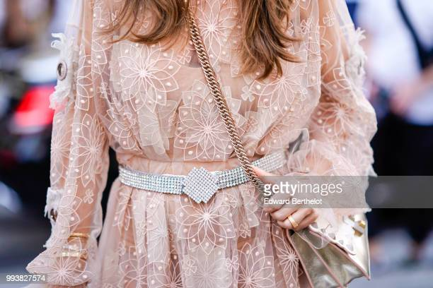 A guest wears a pink lace mesh dress with a glitter belt outside Fendi during Paris Fashion Week Haute Couture Fall Winter 2018/2019 on July 4 2018...