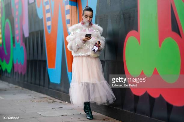 A guest wears a pink lace mesh dress with ruffles is using a smartphone and is smoking during London Fashion Week Men's January 2018 at on January 6...