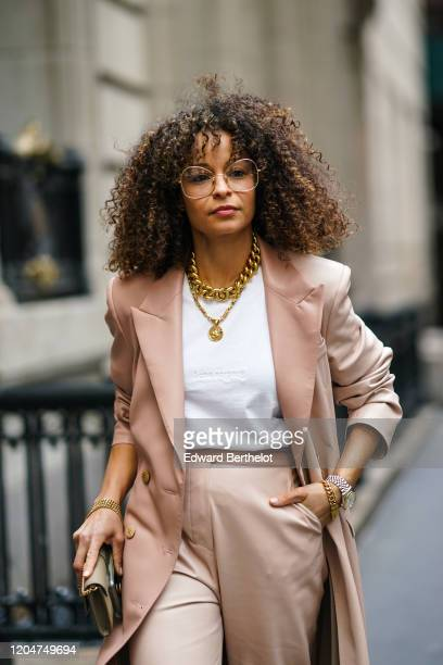 Guest wears a pink long coat, a golden chain necklace, a white t-shirt, pants, a clutch, glasses, outside Cinq a Sept, during New York Fashion Week...