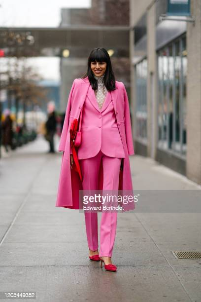 Guest wears a pink long coat, a pink jacket, pink pants, red pointy shoes, a white lace mesh turtleneck top, a bag, during New York Fashion Week Fall...