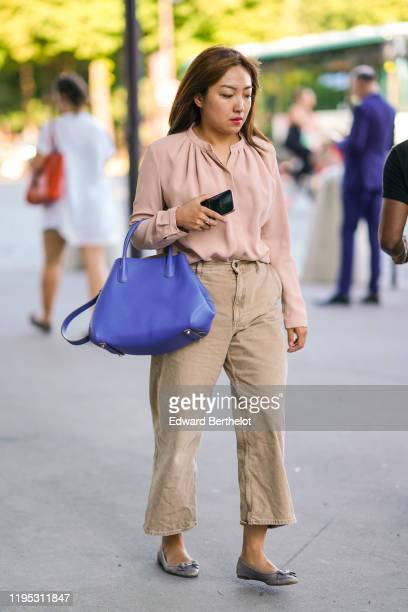 A guest wears a pink long sleeves blouse with a gathered mandarin collar a purple color bag sandcolor denim widelegs crop pants grey flat shoes with...
