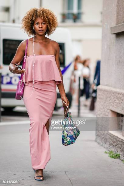 A guest wears a pink offshoulder dress a pink bag and a colorful floer print bag outside the Kenzo show during Paris Fashion Week Menswear...