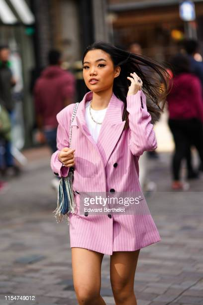 Guest wears a pink oversize blazer jacket dress, a fringed bag, a white t-shirt, a necklace, during London Fashion Week Men's June 2019 on June 08,...