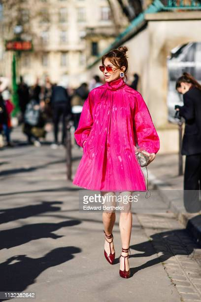 A guest wears a pink pleated dress sunglasses a bag burgundy shoes outside Dior during Paris Fashion Week Womenswear Fall/Winter 2019/2020 on...
