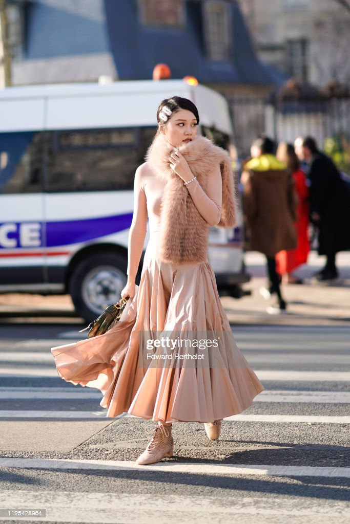 99f224e32614 A guest wears a pink pleated dress with fur