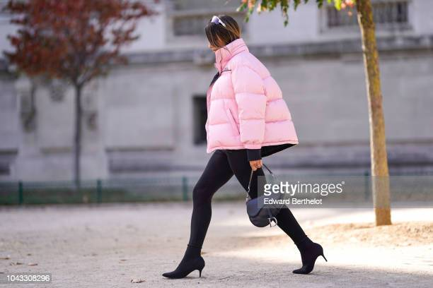 A guest wears a pink puffer jacket a black Dior Saddle bag outside Elie Saab during Paris Fashion Week Womenswear Spring/Summer 2019 on September 29...
