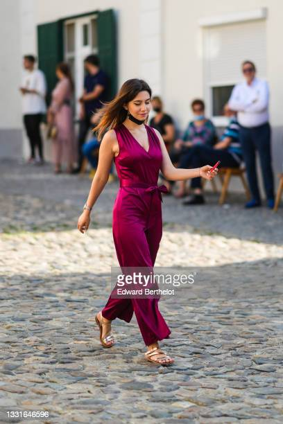 Guest wears a pink / purple shiny V-neck / tank-top / belted / flowing jumpsuit, a black bracelet, a silver watch, a gold shiny leather strappy...