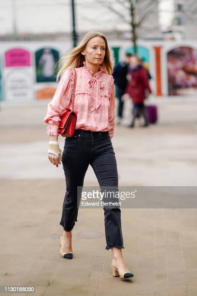 A guest wears a pink ruffled shirt a red bag black denim jeans Chanel slingback shoes during London Fashion Week February 2019 on February 16 2019 in...